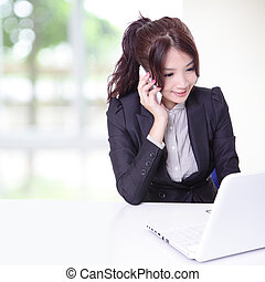 woman speaking mobile phone and using computer