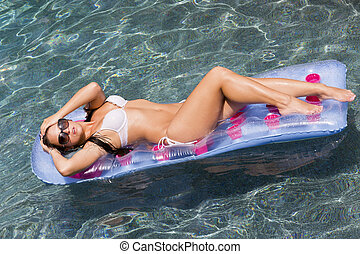 Pool Model - Beautiful bikini model lounges at the pool on a...