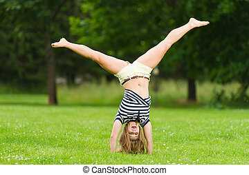 Cartwheel - Young girl doing cartwheel at the park with...
