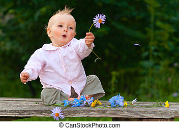 Adorable one-year baby sitting on the table with flowers and...