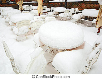 snow-covered tables and chairs