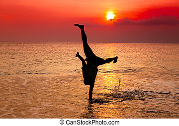 young man hand stand on the beach at sunset