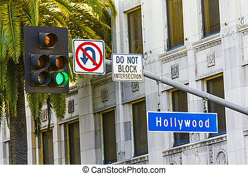 Hollywood Blvd street sign with tall palm trees.