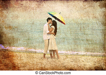 Couple kissing under umbrella at the beach