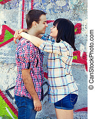 Style teen couple near graffiti background