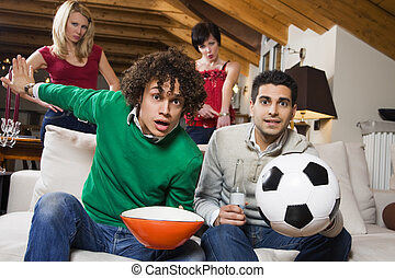 domestic life: group of friend watching soccer on tv while...