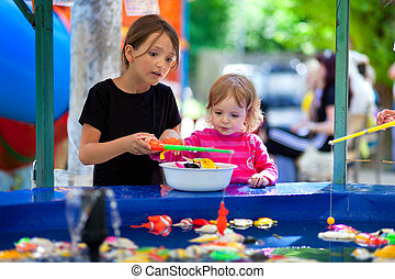 Two sisters, fishin in the paddling pool