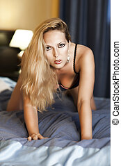 Young sexual woman on bed - Young sexy woman with glamour...