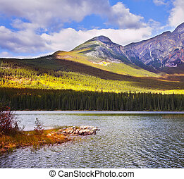 Coast of mountain lake covered by the turned yellow autumn...