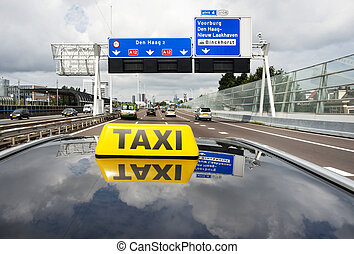 City taxi - Taxi driving on a multiple lane motorway towards...