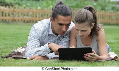 young couple with e-book on nature - beautiful guy and girl...