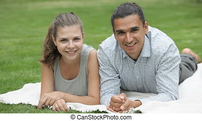 smiling couple on nature - young girl and guy lying on the...