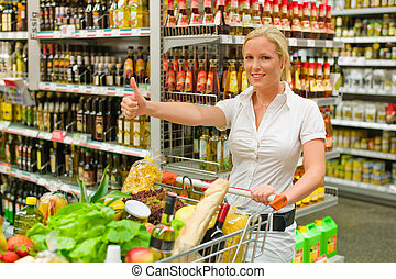 woman at the supermarket - a young woman with a shopping...