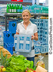 woman buying bottled water in supermarkets - a young woman...