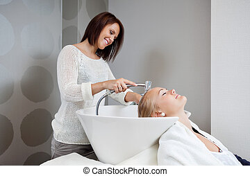 Beautician Washing Hair Of Customer - Beautician smiling...