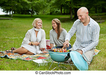 Friends in Park Eating BBQ Picnic