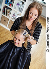 Beautician Applying Hair Colour To Woman - High angle view...