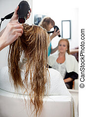 Drying Hair With Blow Dryer - Hairdressers hands drying long...