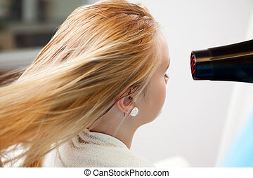 Womans Hair Being Blow Dried - Blond hair of a young woman...