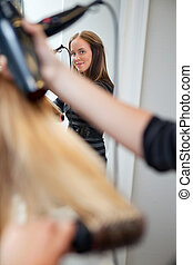 Hair Stylist Holding Blow Dryer - Mirror reflection of a...