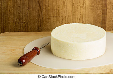 Round block of cheese with knife