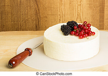 Block of cheese with berries and a knife