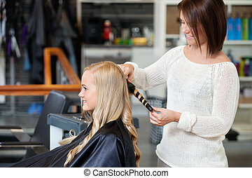 Woman Getting Her Hair Curled - Young woman getting her...