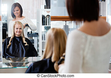 Woman Getting a New Hairstyle - Mirror reflection of young...
