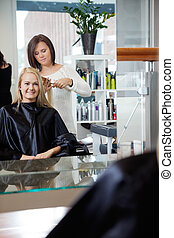 Hairdresser Giving Haircut To Woman