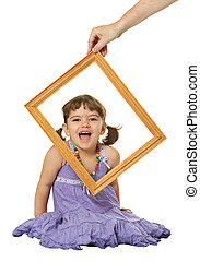 Happy little girl looking through the frame isolated on...