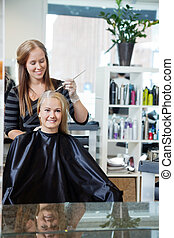 Woman Getting Hair Highlighted - Mirror reflection of...