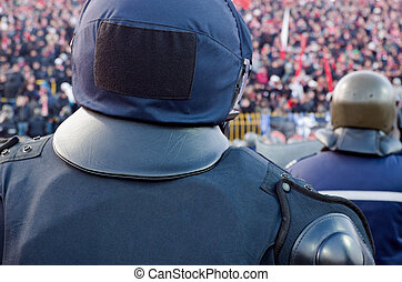 Back of policeman guarding fans - Shot of the back of...
