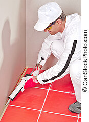 worker in white clouts lays silicone sealant corner wall...