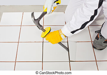 Worker with hammer removes old white tiles from floor -...
