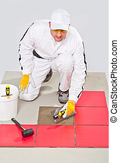 Appling Tile Adhesive with Notched Trowel on a Floor
