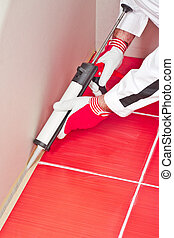worker applies silicone sealant on corner wall tiles -...