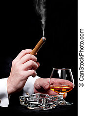 Person holding a cigar and drink cognac