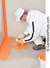 construction worker in white coveralls waterproofing applied by brush on the floor and walls of the bathroom, before fixing ceramic tiles
