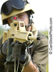 Soldier in helmet targeting with a rifle