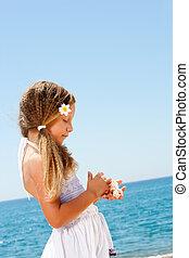 Cute girl holding shells on sunny beach.