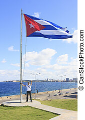 Man with a flag of Cuba - Man with a flag on the site of...