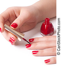 Manicurist applying red nail polish on female fingers