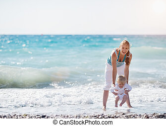 Mother and baby playing with sea waves