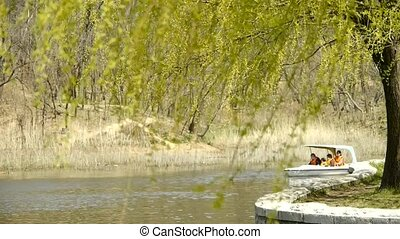 Dense willows by sparkling lake,Tourists cruise ships on...