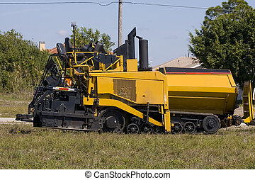 An asphalt paving machine waits on the operator that is in a...