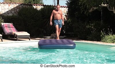 Humorous Jump - Video of funny man jumping on water mat in...