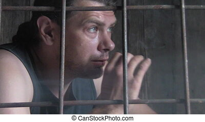 male behind bars, smoking, looking around, speculates