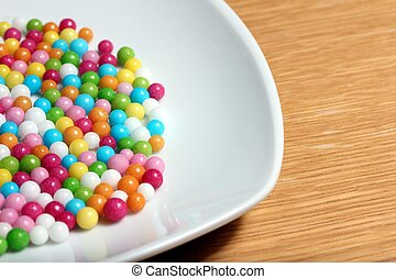 colored sugar balls on a white plate