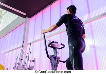 Elliptical Gym - Man back, training cardio on the elliptical...
