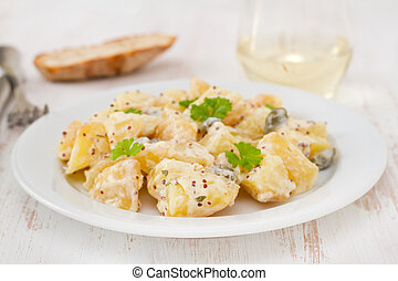 potato salad with sauce on the white plate